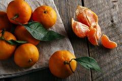 Dojrzali tangerines z liśćmi na drewnianym stole Obrazy Stock