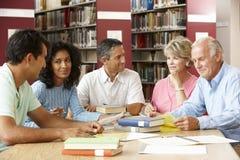 Dojrzali ucznie pracuje w bibliotece obrazy stock