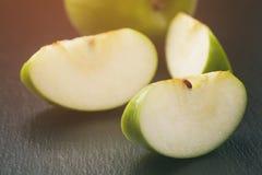 Dojrzali zieleni jabłka pokrajać na łupek desce zdjęcie stock
