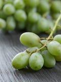 Dojrzali zieleni winogrona na czarnym drewno stole Obraz Stock