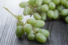 Dojrzali zieleni winogrona na czarnym drewno stole Zdjęcie Royalty Free