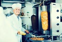 Dojrzały mężczyzna szef kuchni jest ubranym jednolitego narządzania kebab Zdjęcia Royalty Free