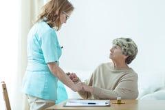 Dokter die haar oude patiënt bezoeken stock afbeeldingen