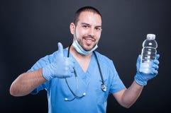 Dokter het dragen schrobt het tonen van water en gelijkaardig gebaar royalty-vrije stock fotografie