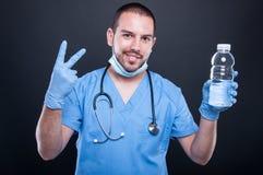 Dokter het dragen schrobt het tonen van water en nummer twee stock foto