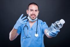 Dokter het dragen schrobt het tonen van water en nummer vier royalty-vrije stock foto's