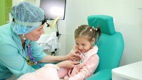 Dokter het luisteren de kinderenlongen met stethoscoop, het behandelingsziekenhuis, kinderen` s kliniek, jong geitje waren zieke  stock videobeelden