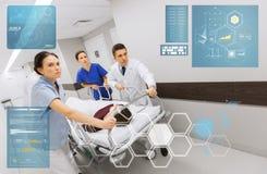 Dokters met vrouw op het ziekenhuisgurney bij noodsituatie royalty-vrije stock afbeelding