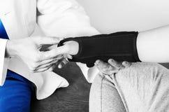Doktor überprüft das Handgelenk zu einem Patienten, nachdem er eine Manschette in Schattenbild, in Farbe und in Schwarzweiss eing Lizenzfreies Stockbild