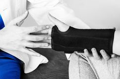 Doktor überprüft das Handgelenk zu einem Patienten, nachdem er eine Manschette in Schattenbild, in Farbe und in Schwarzweiss eing Lizenzfreie Stockfotos