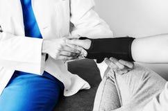 Doktor überprüft das Handgelenk zu einem Patienten, nachdem er eine Manschette in Schattenbild, in Farbe und in Schwarzweiss eing Stockfoto