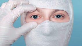 Doktor überprüft die geduldigen Augen Ärztliche Untersuchung Hand in den medizinischen Handschuhen und Kopf im Verband stockbild