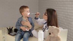 Doktor überprüft die Kehle des Jungen mit Taschenlampe stock footage