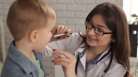 Doktor überprüft Kehle und Mund zu einem kleinen Kind stock video