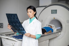 Doktor Analyzing X-ray While Patient, der auf CT-Scan-Maschine liegt Stockbilder