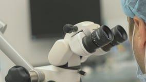 Doktor använt mikroskop Tandläkaren behandlar patienten i modernt tand- kontor Orthodontistarbete med assistenten funktion stock video