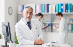 Doktor am Aufnahmeschreibtisch Stockbilder