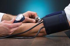 Doktor Checking Blood Pressure des Patienten bei Tisch lizenzfreie stockfotografie