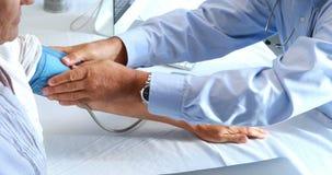 Doktor Checking Blood Pressure eines Patienten stock footage