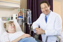 Doktor Checking Up On Patient im Krankenhaus lizenzfreie stockbilder