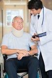 Doktor Communicating With Patient auf Rollstuhl lizenzfreie stockfotografie