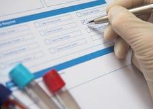 Doktor Completing ein Blutprobe-Formular stockfotografie