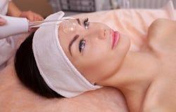 Doktor-cosmetologisten gör den tillvägagångssättMicrocurrent terapin av den ansikts- huden på pannan royaltyfri foto