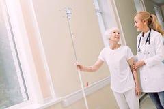 Doktor, der älterem Patienten mit Tropfenzähler hilft lizenzfreie stockbilder