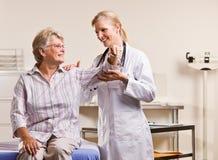 Doktor, der älteren Frauenarm überprüft Lizenzfreie Stockfotografie