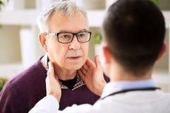 Doktor, der alte geduldige Lymphdrüsen überprüft Stockbilder