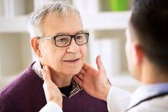 Doktor, der alte geduldige Lymphdrüsen überprüft Stockfoto