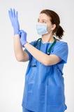 Doktor, der auf blaue chirurgische Handschuhe sich setzt Lizenzfreies Stockbild