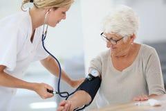 Doktor, der auf Blutdruck des Patienten überprüft Stockfotos