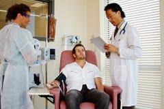 Doktor, der auf geduldigem Status überprüft Lizenzfreies Stockbild