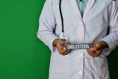 Doktor, der auf grünem Hintergrund steht Selektiver Fokus in der Hand Hoher Colesterol-Papiertext lizenzfreie stockfotos