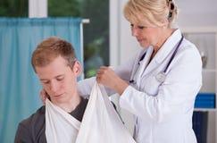 Doktor, der auf Riemen Patienten vorlegt lizenzfreies stockbild