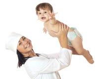 Doktor, der Baby über seinem Kopf hält. Lizenzfreies Stockbild