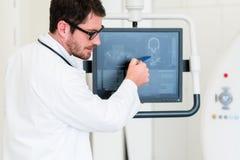 Doktor, der Bild von MRI-Scan auf Schirm erklärt Stockbild