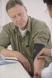 Doktor, der Blutdruck überprüft Lizenzfreie Stockfotos