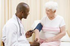 Doktor, der Blutdruck der Frau überprüft Stockbilder
