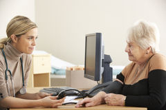 Doktor, der Blutdruck der älteren Frau nimmt Stockfotografie