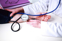 Doktor, der Blutdruck nimmt Lizenzfreies Stockfoto