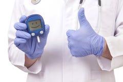 Doktor, der Blutzuckermeter hält. Zeigen des OKAYzeichens Lizenzfreies Stockfoto