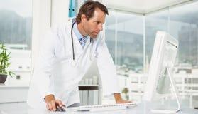 Doktor, der Computer im Ärztlichen Dienst verwendet stockfotografie