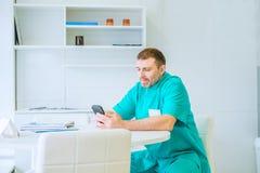 Doktor, der das intelligente Mobiltelefon, sitzend im medizinischen Raum im Krankenhaus, elektronisches Gesundheitsaktesystem EHR Stockfotografie
