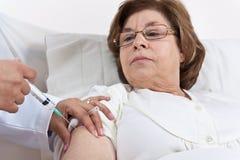Doktor, der dem älteren Patienten Einspritzung gibt Stockfoto