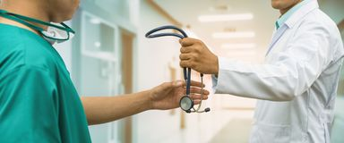 Doktor, der dem Chirurgen Referral Stethoskop gibt Stockfoto