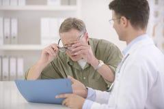 Doktor, der dem kurzsichtigen Patienten Ergebnisse zeigt Lizenzfreies Stockfoto