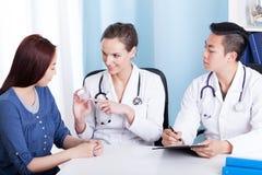 Doktor, der dem mongolischen Patienten Medizin gibt Stockfotos