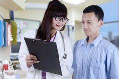 Doktor, der dem Patienten Bearbeitungsergebnis zeigt Lizenzfreie Stockfotografie